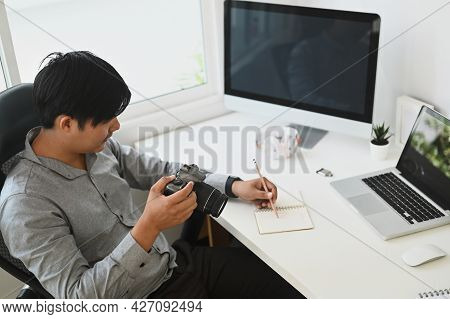 A Young Photographer Reviewing His Captured Photos In His Camera While Sitting At His Desk Inside Th