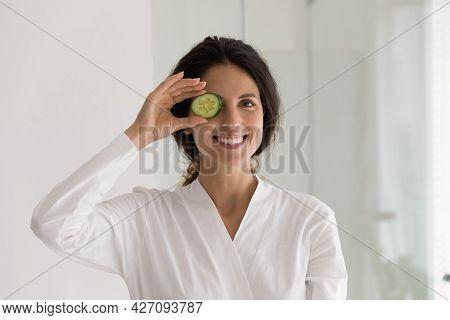 Pretty Millennial Hispanic Woman In Bathrobe Demonstrate Juicy Cucumber Slice