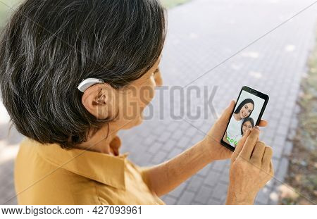 Senior Woman With A Hearing Aid Behind The Ear Communicates With Her Daughter And Granddaughter Via
