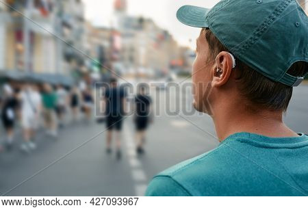 Human Life With A Hearing Aid. Young Man With A Hearing Aid Behind The Ear In A Noisy City Hears Peo