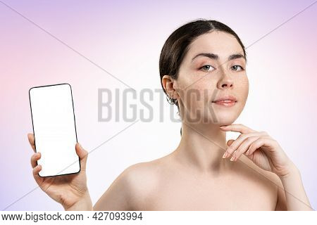 Portrait Of A Beautiful Woman Holding A Smartphone With A White Screen. Mock Up. Light Lilac Backgro