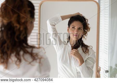 Young Latina Female In Bathrobe Looking At Mirror Creating Hairdo