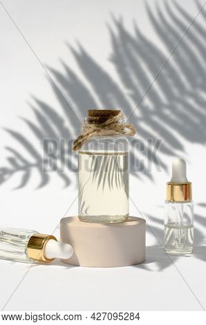 A Transparent Bottle Of Essential Oil In The Shade Of A Palm Tree. Body Care Concept, Natural Cosmet