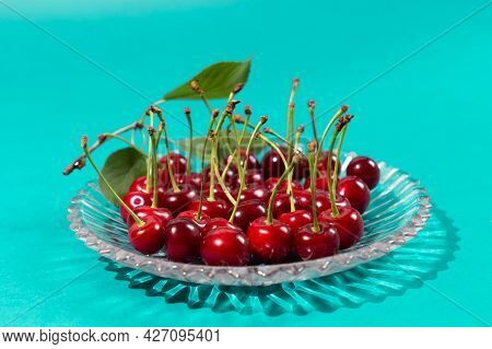 Ripe Cherry On Plate On Blue Background. Food For A Good Sleep. Cherry Berries Helps With Insomnia.