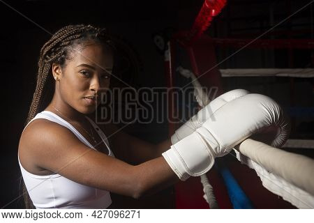 Young Black Female Athlete With Boxing Gloves Looking At Camera With Boxing Ring Background