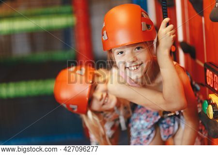 Two Happy Little Girls In Red Helmets Climbing The Wall In Bouldering Center. School Girls Smiling A