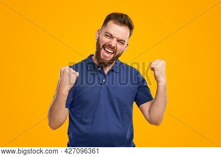 Optimistic Adult Bearded Guy In Casual Shirt Clenching Fists And Screaming Happily While Rejoicing O