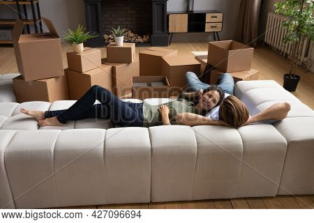 Young Couple Take Break In Renovating Home Rest On Couch