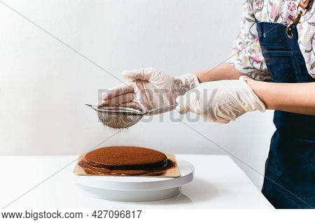 Woman Wearing Apron Powdering Chocolate Cake With Cocoa Powder.