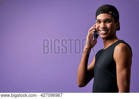 Portrait Of Transgender Young Man Talking Mobile In Black Casual Dress. Latino Trans Gender Model