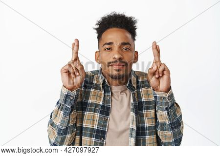 Close Up Of Nervous Hopeful Man, African American Guy Cross Fingers Good Luck, Waiting For Dream Com