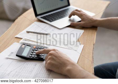 Close Up Young Man Using Calculator Summarizing Domestic Utility Bills.