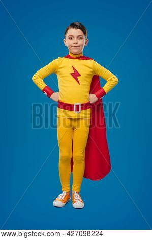 Full Body Of Determined Brave Little Boy In Yellow Superhero Costume And Red Cloak Standing, With Ha