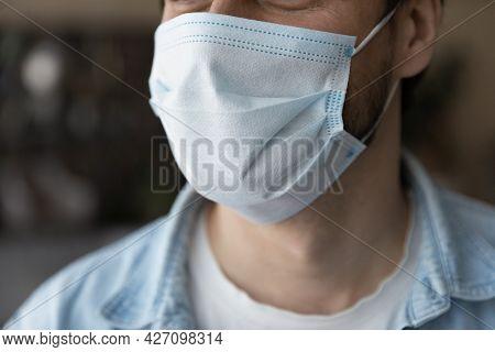 Close Up Young Man Wearing Medical Disposable Facemask.