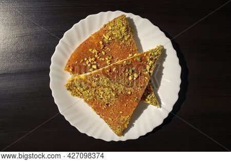 Slices Of Eastern Dessert Kunafa On A White Plate On Dark Black Background. Top View. Arabic Cheese