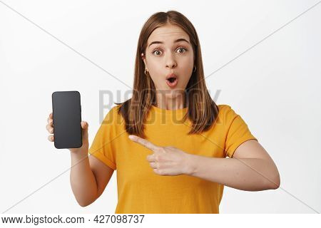 Wow Look At Screen. Impressed Young Woman Pointing Finger At Smartphone Screen Sale, Gasping Amazed,