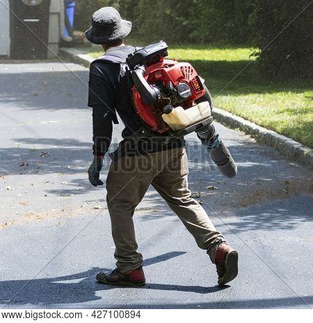 A Professional Landscaper Clearing A Driveway Of Dirt And Dust With An Leaf Air Blower That Is Strap