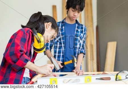 Teenager Boy With His Little Sister Building A Workshop Together In A Carpentry Workshop. Children T
