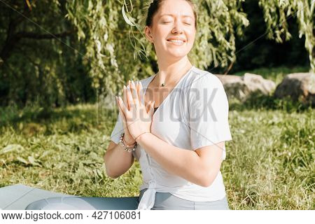 Close-up Portrait Of Happy Smiling Young Woman Practicing Meditation And Yoga Outdoors In Morning. G