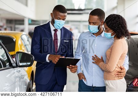 Salesperson In Medical Mask Consulting Black Spouses In Dealership Center