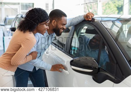 New Car. Excited Black Spouses Looking At New Automobile In Dealership Office