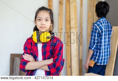 Girl Standing With Arms Crossed Looking At Camera Blurred Teenager Boy In A Carpentry Workshop. Chil