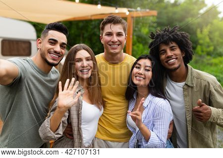 Multiethnic Young Friends Taking Selfie Together Near Motorhome, Making Different Gestures And Smili