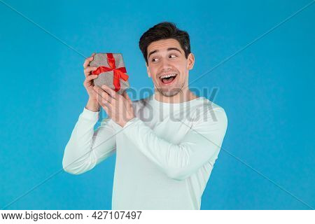 Handsome Man Holding Gift Box On Blue Studio Background And Smiles To Camera. Happy European Guy Rec