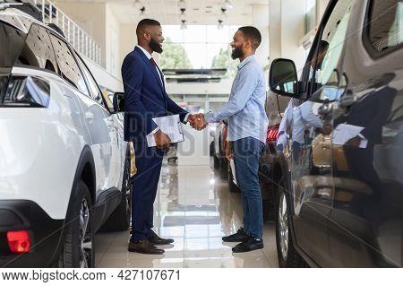 Black Car Seller Shaking Hands With Customer In Modern Dealership Center