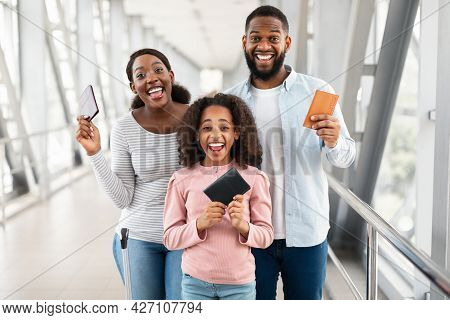 Happy Excited Black Family Traveling, Holding Documents In Airport