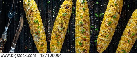 Top Down View Of Ears Of Corn On The Cob On A Grill Pan, Garnished With Seasoning And Herbs.