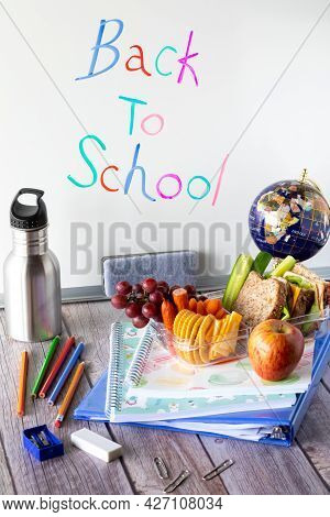Close Up Of Various School Supplies And A Lunch Kit Against A Whiteboard. Back To School Concept.