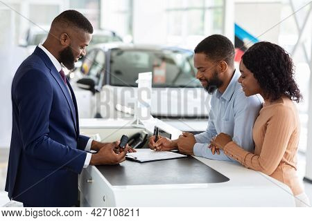 Buying New Car. African American Couple Signing Papers In Dealership Center