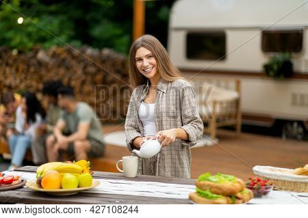 Pretty Caucasian Woman Pouring Tea, Making Breakfast Near Motorhome, Camping With Her Multinational