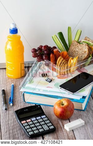 Close Up Of A Variety Of School Supplies Along With Lunch In A Lunch Box. Back To School Concept.