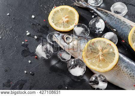 3 Raw Fish, Mackerel ,  Ice,   Lemon  On A Dark Background, Seafood