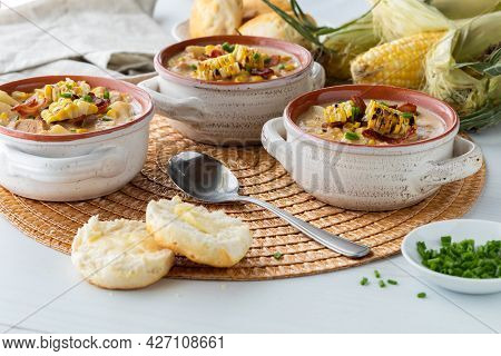 Close Up View Of Soup Crocks Filled With Chicken And Corn Chowder Garnished With Grilled Corn, Bacon
