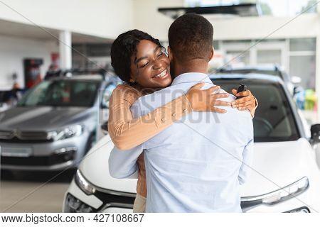 Grateful Black Wife Embracing Husband After Buying New Car In Dealership Showroom
