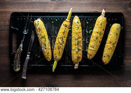 Top Down View Of Corn On The Cob On A Black Grill Pan, Topped With Seasoning And Herbs.