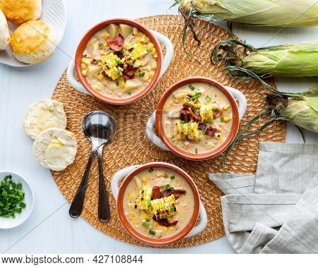 Top Down View Of Chicken And Corn Chowder In Soup Crocks Topped With Grilled Corn And Bacon, Ready F
