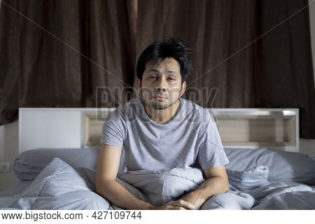 Asian Man With Hangover Sitting On Bed In Room