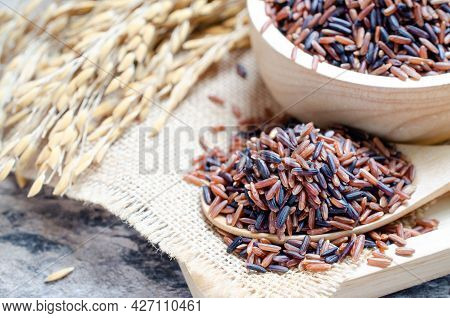 Closed Up Dry Organic Mixed Brown And Rice Berry Seed Pile In Wooden Spoon And Bowl On Sack Fabric O
