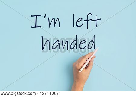 Text I Am Left Handed And Left Hand With Pen Over Blue Background. International Left Handers Day Id
