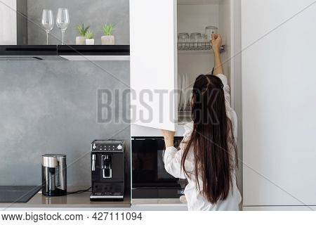 Rear View Of Woman In Homewear Taking Glass Cup From Shelf In White Cupboard With Dishware In Minima