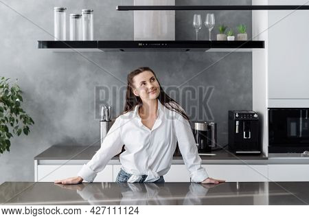 Young Beautiful Dreamy Woman In Casual Outfit Standing At Table In Modern Fully Furnished Kitchen An