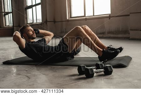 Side View Of Athletic Male Doing Abdominal Crunches While Lying On Mat And Training In Spacious Shab