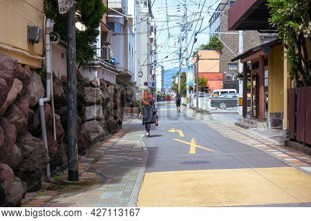 Beppu, Kyushu, Japan, May 14, 2021: A Small And Narrow Street In The Seaside Town Of Beppu And A Few