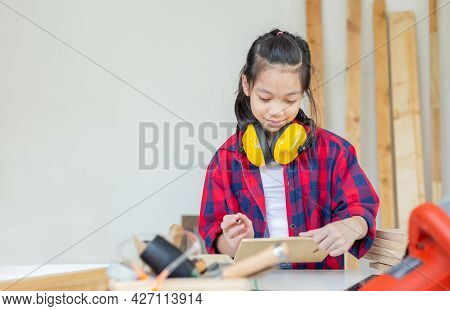 Happy Girl Standing With Noise Reduction Earmuffs In A Carpentry Workshop. Children Learning In The