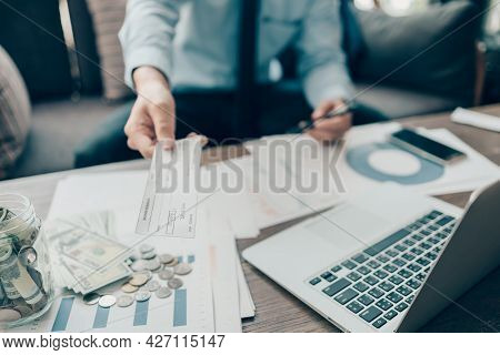 A Businessperson's Hand Giving Cheque To Customer And Dollar Bill, Coin, Laptop And Graph Chart On T