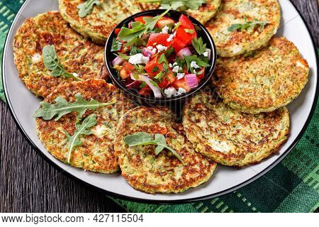 Close-up Of Zucchini Fritters With Dill Served With Fresh Feta Cheese Tomato Salad On A Plate On A W